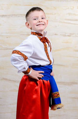 dance preteen: Proud young boy in a colorful dance or pantomime costume standing with his hands on his hips grinning at the camera