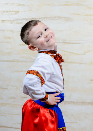 jaunty: Proud young boy in a colorful dance or pantomime costume standing with his hands on his hips grinning at the camera