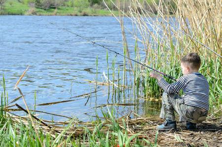 Twee jonge broers en zussen die hun Hengels om vis te vangen op de rivier op een zeer zonnige dag.
