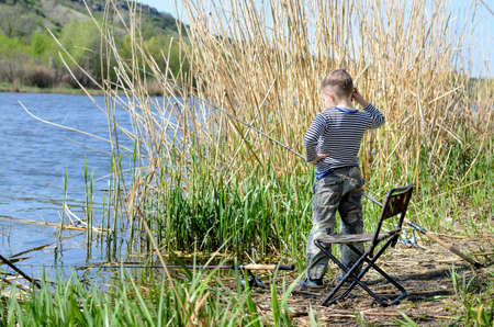 eyeing: Young boy fishing on a lake shore standing eyeing the water with his rod and chair alongside him