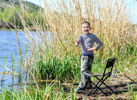 pitched: Happy excited young boy giving a thumbs up as he fishes at the side of a lake with his rod, reel and comfortable chair pitched alongside a clump of reeds