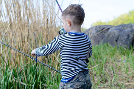 spinning reel: Young boy holding up his fishing rod and spinning reel as he prepares to cast in from a lake shore Stock Photo