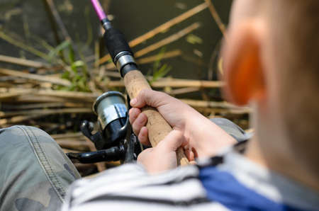 spinning reel: Young boy fishing with a spinning reel and rod, close up of his hands on the cork handle