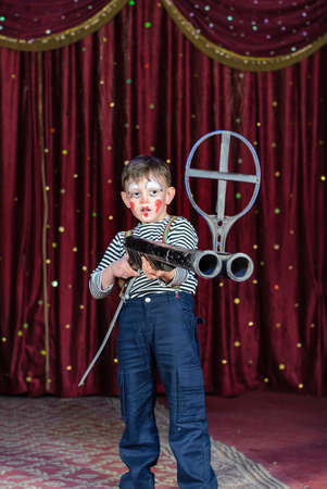 stage make up: Young Boy Wearing Clown Make Up Standing on Stage Aiming Large Prop Shot Gun Rifle in front of Red Curtain