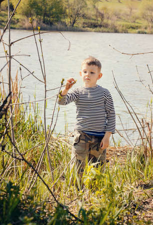 young boy: Young Boy Wearing Striped Shirt Stopping to Smell and Examine Plant Growing Amongst Reeds Along Shore of Lake Stock Photo