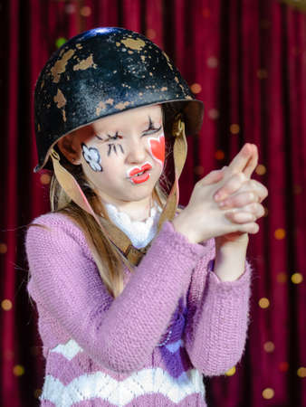 waist up: Waist Up Portrait of Young Blond Girl Wearing Clown Make Up and Military Helmet Making Gun Out of Clasped Hands and Aiming with Squinted Eyes