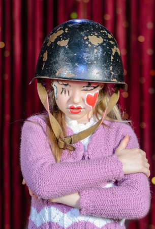 glaring: Young Girl Wearing Clown Make Up and Military Helmet Looking Stern Standing with Arms Crossed and Glaring at Camera on Stage in front of Red Curtain Stock Photo