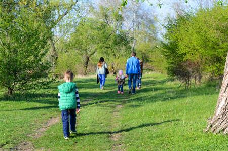 niños caminando: Vista posterior de la familia que recorría junta al aire libre en Overgrown Dual Track Carretera de campo a través de árboles verdes