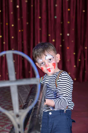 stage make up: Serious Young Boy Wearing Clown Make Up Aiming Over Sized Rifle Gun Toward Camera and Standing on Stage in front of Red Curtain Stock Photo
