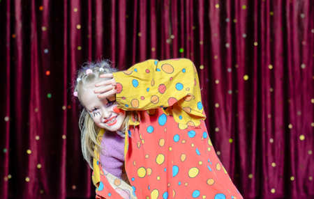 stage costume: Young Blond Girl Wearing Clown Make Up and Polka Dot Costume Shielding Eyes from Bright Stage Lights in front of Red Curtain Stock Photo