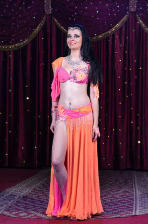 belly dancer: Full Length Portrait of Smiling Exotic Female Belly Dancer Wearing Bright Pink and Orange Costume Standing with Leg Revealed on Stage with Red Curtain Stock Photo