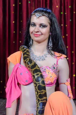 stage costume: Exotic Female Dance Performer in Brightly Colored Costume with Large Constrictor Snake on Stage in front of Red Curtain