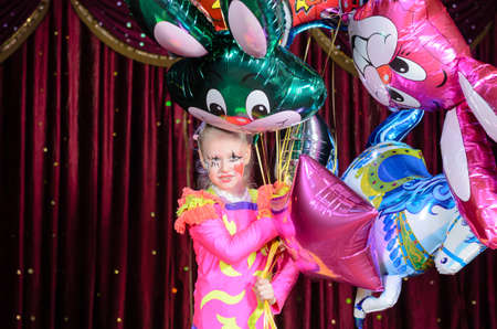 stage costume: Young Smiling Blond Girl Wearing Bright Costume and Clown Make Up Holding Large Bunch of Foil Balloons Standing on Stage in front of Red Curtain