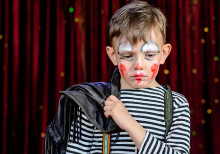 stage make up: Head and Shoulders of Young Boy Wearing Clown Make Up Holding Leather Jacket Over Shoulder and Looking Solemnly Downward on Stage with Red Curtain Stock Photo