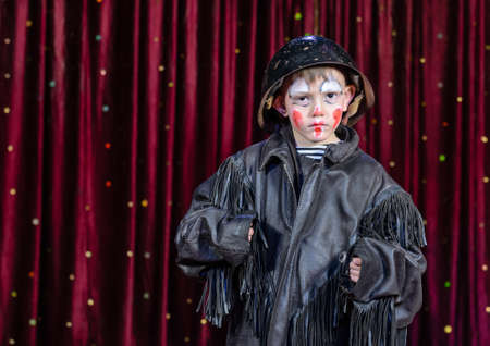 stage make up: Waist Up Portrait of Young Boy Wearing Clown Make Up, Leather Jacket and Helmet Staring Seriously at Camera on Stage with Red Curtain