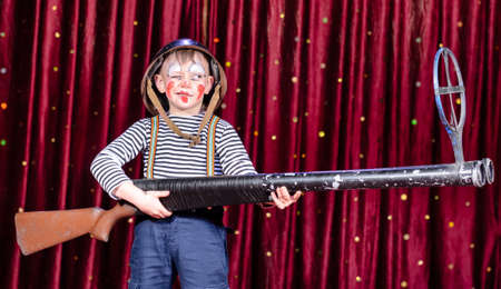 over sized: Young Boy Wearing Clown Make Up and Military Helmet Standing on Stage with Red Curtain Aiming Over Sized Prop Rifle Gun Toward Camera