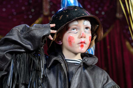 sized: Head and Shoulders Close Up of Young Boy Wearing Clown Make Up, Leather Jacket and Helmet Saluting and Staring Upward as if at Authority Figure