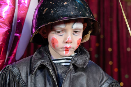 Head and Shoulders Close Up of Young Boy Wearing Clown Make Up, Leather Jacket and Helmet Staring Solemnly Downward on Stage photo