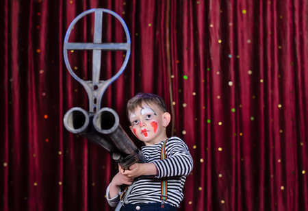 over sized: Serious Young Boy Wearing Clown Make Up Aiming Over Sized Rifle Gun Toward Camera and Standing on Stage in front of Red Curtain Stock Photo