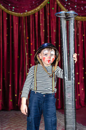 role play: Young Boy Wearing Clown Make Up and Military Helmet Standing on Stage with Large Prop Shot Gun Rifle in front of Red Curtain