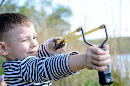 projectile: Young Smiling Boy Wearing Striped Shirt Holding Sling Shot with Rubber Bands Drawn Back in Anticipation of Catapulting Projectile Outdoors Near Lake