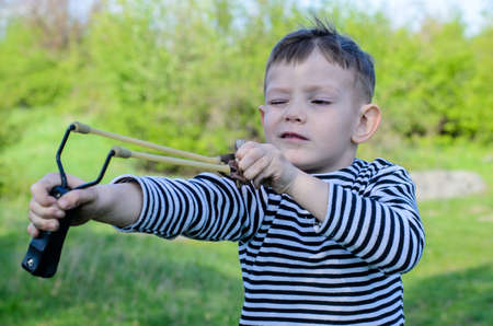 projectile: Waist Up of Young Boy Wearing Striped Shirt Holding Sling Shot with Rubber Bands Pulled Back in Anticipation of Catapulting Projectile