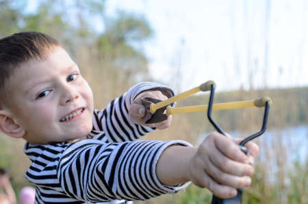 Young Smiling Boy Wearing Striped Shirt Holding Sling Shot with Rubber Bands Drawn Back in Anticipation of Catapulting Projectile Outdoors Near Lake