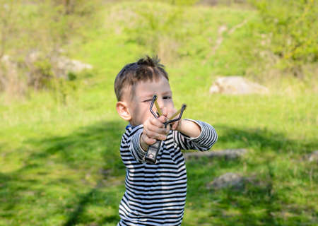 projectile: Close Up Side View of Boy Wearing Striped Shirt Holding Sling Shot with Rubber Bands Pulled Back in Anticipation of Catapulting Projectile Stock Photo