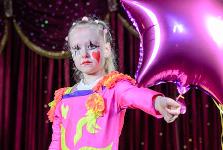 stage costume: Head and Shoulders Portrait of Young Blond Girl Wearing Clown Make Up and Costume Holding Star Shaped Balloon on Stage in front of Red Curtain