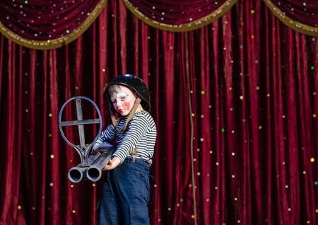 stage make up: Young Boy Wearing Clown Make Up and Military Helmet Standing on Stage with Red Curtain Aiming Over Sized Prop Rifle Gun Toward Camera