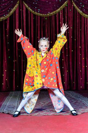 Volledige lengte van jonge blond meisje dat Clown Make-up en Stip kostuum staande met open armen en benen op Stadium met rood gordijn Stockfoto