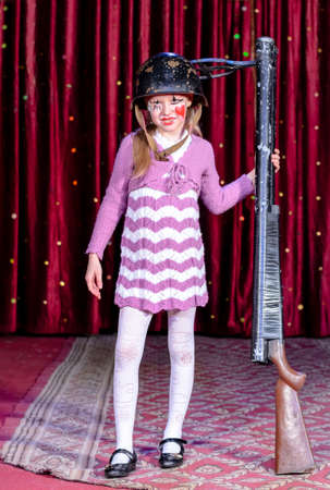 girl gun: Full Length Portrait of Girl Wearing Clown Make Up, Striped Dress and Helmet Holding Over Sized Gun on Stage in front of Red Curtain Stock Photo