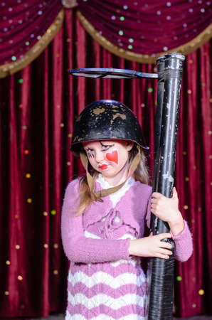 over sized: Full Length Portrait of Girl Wearing Clown Make Up, Striped Dress and Helmet Holding Over Sized Gun on Stage in front of Red Curtain Stock Photo