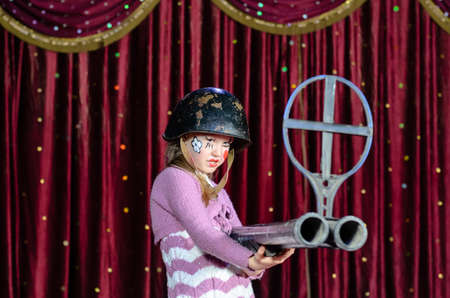 sized: Serious Young Blond Girl Wearing Clown Make Up and Military Helmet Aiming Over Sized Rifle Gun Toward Camera and Standing on Stage in front of Red Curtain