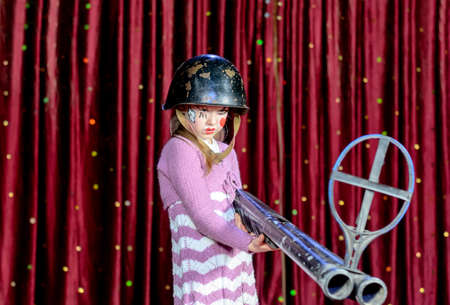 girl with gun: Serious Young Blond Girl Wearing Clown Make Up and Military Helmet Aiming Over Sized Rifle Gun Toward Camera and Standing on Stage in front of Red Curtain