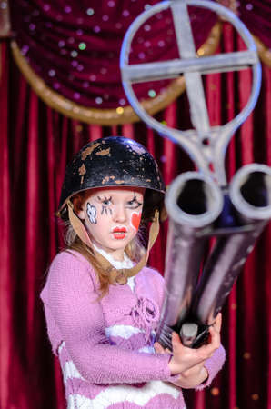 make believe: Serious Young Blond Girl Wearing Clown Make Up and Military Helmet Aiming Over Sized Rifle Gun Toward Camera and Standing on Stage in front of Red Curtain