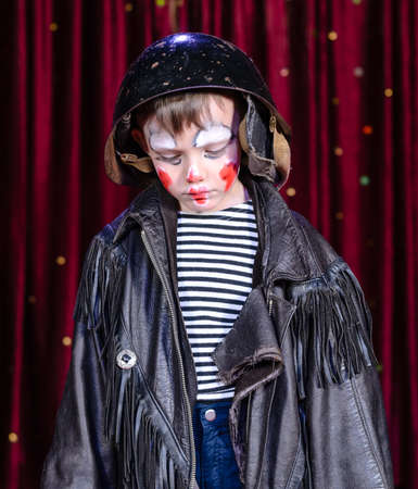 stage make up: Head and Shoulders Close Up of Young Boy Wearing Clown Make Up, Leather Jacket and Helmet Staring Solemnly Downward on Stage