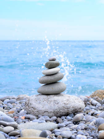 splash back: Stack of Stones in Different Sizes Near the Beautiful Blue Ocean, with Splash of Water at the Back, on a Tropical Climate