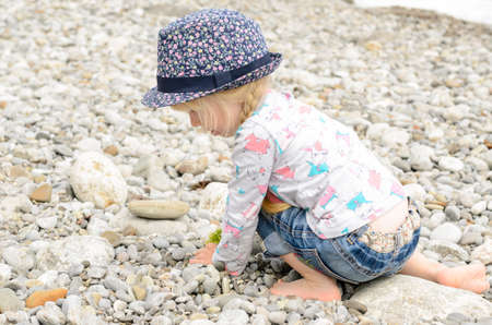 Young Blond Girl in Summer Outfit Playing with Small Stones at the Beach Alone photo