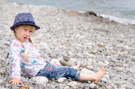 Young Blond Girl with Hair in Braids Sitting on Rocky Beach Wearing Floral Print Hat and Looking Worried photo