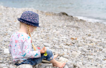 Young Blond Girl with Hair in Braids Sitting on Rocky Beach Wearing Floral Print Hat and Looking Out at View of Ocean photo