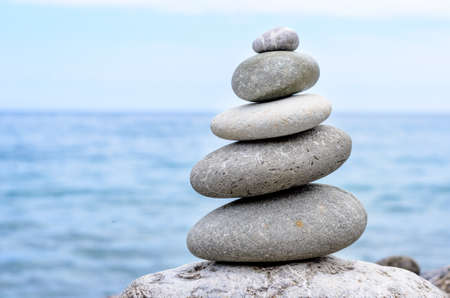 smallest: Conceptual Stack of Six Dry Stones at the Sea, from Biggest to Smallest Size Stock Photo