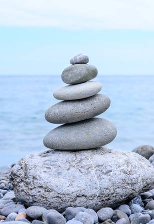 emphasizing: Close up Conceptual Piled Stones with Different Sizes at the Beach, Emphasizing Perfect Balance