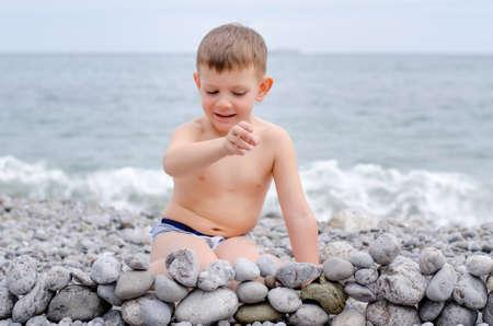 niño sin camisa: Sin camisa joven niño sentado en la playa rocosa y jugar con las rocas, creando pequeños muro de piedra con vista de agua en el fondo