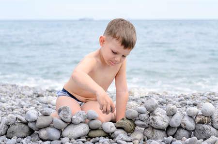 ni�o sin camisa: Joven descamisado Muchacho que se sienta en la playa rocosa y Jugar con las rocas, creando peque�os Pared de piedra con vista de agua en el fondo Foto de archivo