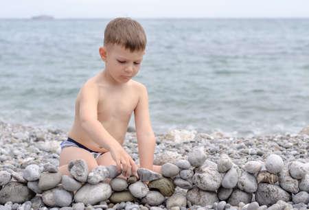 niño sin camisa: Joven descamisado Muchacho que se sienta en la playa rocosa y Jugar con las rocas, creando pequeños Pared de piedra con vista de agua en el fondo Foto de archivo