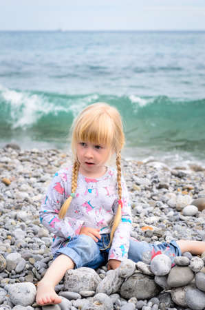 Young Blond Girl with Hair in Braids Building Stone Wall on Rocky Beach with Water and Waves in Background photo