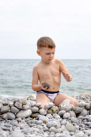 kids playing beach: Young Shirtless Boy Sitting on Rocky Beach and Playing with Rocks, Creating Small Stone Wall with View of Water in Background Stock Photo