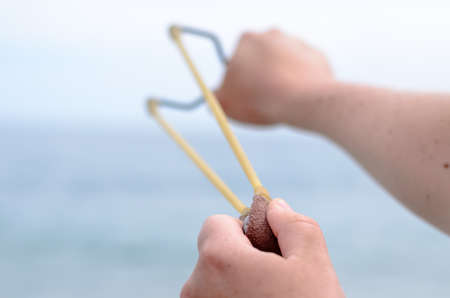 shooter: Close up Hand of a Man Stretching Bands of his Stone Shooter Stick Towards the Ocean.