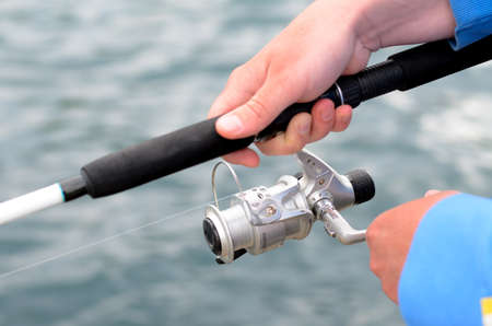 spinner: Fisherman using a fishing rod and spinner reel as he fishes from the seashore, close up of his hands and the tackle Stock Photo